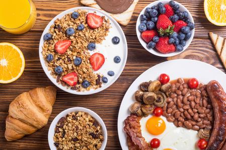 Healthy balanced english breakfast with yogurt , berries , fruit , coffee and juice