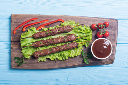 Caucasian traditional food . Shish kebab or lula-kebab with vegetables and sauce