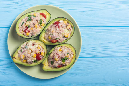 Avocado stuffed with salad from vegetables , parsley and eggs
