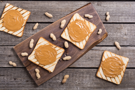 Peanut butter sandwiches or toasts on wooden background