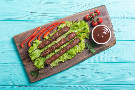 Caucasian traditional food . Shish kebab or lula-kebab with vegetables and sauce