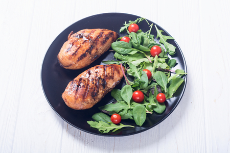 Grilled chicken with spinath and tomatoes salad . BBQ food background