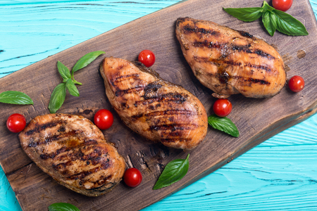 Grilled chicken breast ( fillet ) with basil and tomatoes . BBQ background Stock Photo