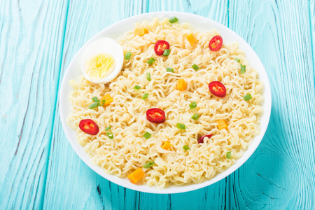 Instant noodles in bowl with chili peppers, eggs , onion and carrots Stock Photo