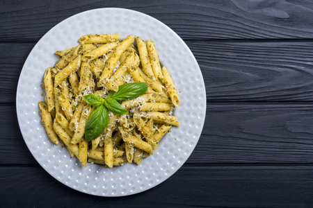 Italian penne pasta with sauce pesto . Food background