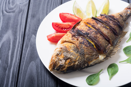 Fried fish dorado with lime , tomatoes and spinach . Sea food background