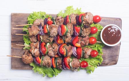 Grilled pork shish or kebab on skewers with vegetables . Food background shashlik Stock Photo