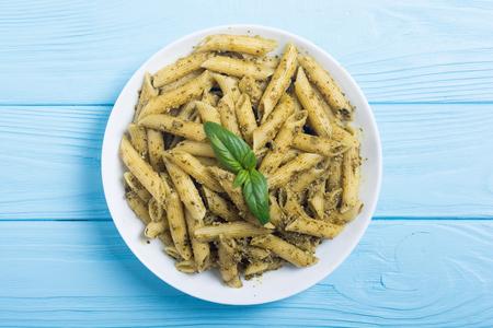 Italian penne pasta with sauce pesto . Food background