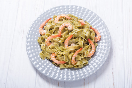 Pasta tagliatelle with sauce pesto and shrimps . Italian food background Banque d'images
