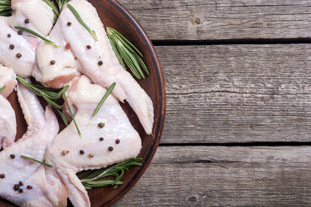 Chicken raw wings with rosemary , garlic , pepper and salt . Ingredient for preparation