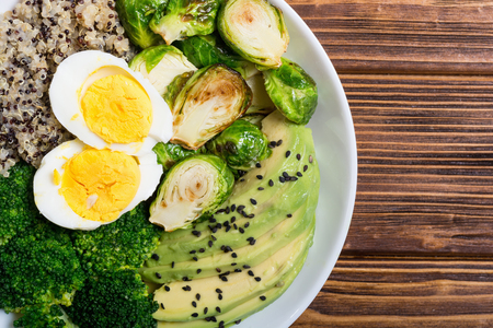 Buddha bowl with quinoa , eggs , avocado , brussels sprouts and broccoli . Food vegan salad on wooden backgground 版權商用圖片