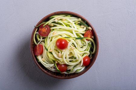 Zucchini pasta noodles with tomatoes . Healthy vegetarian food 免版税图像