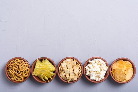 Frame . Mix of snacks : pretzels , crackers , chips nachos and pop corn