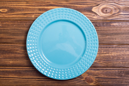 Empty blue plate on wooden table . Top view background