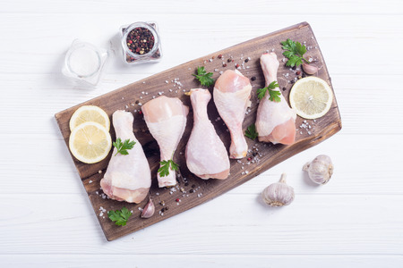 Raw chicken legs with spices and parsley. Food background Stock fotó