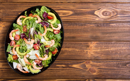 Mix of salad with shrimps , avocado and cherry tomatoes . Healthy food background