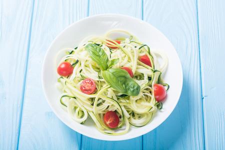 ズッキーニパスタ麺とトマト.ヘルシーベジタリアン料理