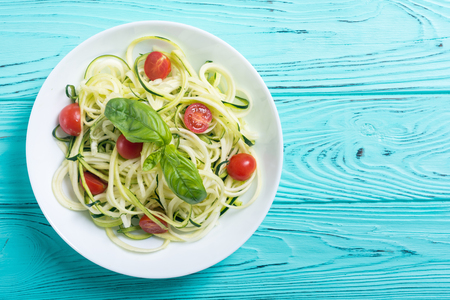 Zucchini pasta noodles with tomatoes . Healthy vegetarian food Stock Photo