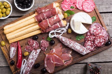 Set of sausages ( ham , salami , jamon ) and olives on wooden board