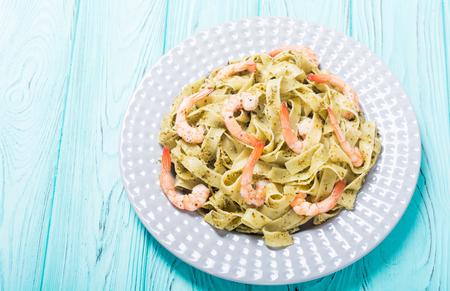 Pasta tagliatelle with sauce pesto and shrimps . Italian food background Stock Photo