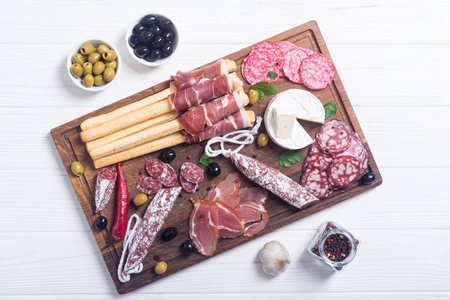 Set of sausages ( ham , salami , jamon ) and olives on wooden board