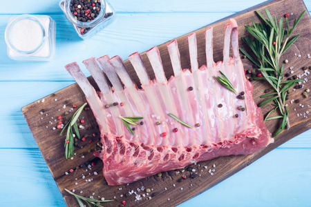 Raw rack of lamb with spices and herbs . Food background