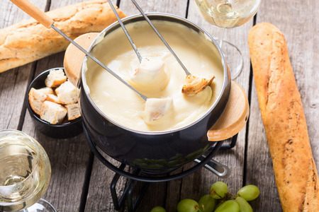 Cheese fondue with bread wine and grape . Swiss winter food