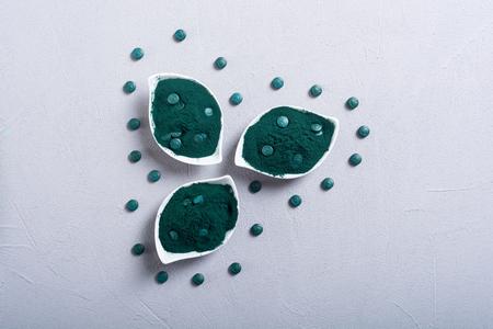 Ground spirulina and spirulina in pills . Healthy vegan superfood background