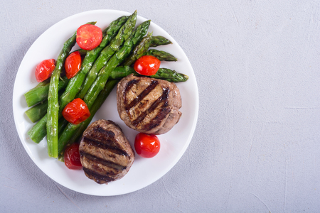 Grilled filet mignon with asparagus and tomatoes . Beef sreak on rustic background