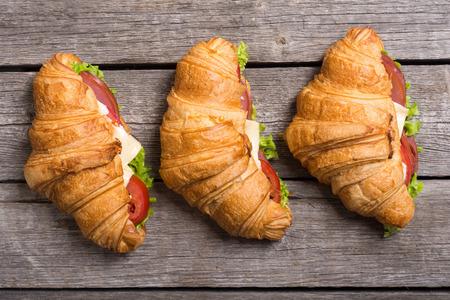 Panino croissant francese con lattuga , formaggio , pomodori e prosciutto