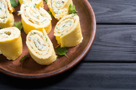 Homemade Eggs omelet rolls with parsley and cream cheese . Food background breakfast