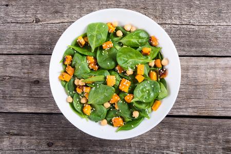 Assiette avec salade d'automne au potiron , épinards , pois chiches et sésame . Fond végétalien de nourriture