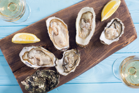 Fresh Oysters with lemon and white wine . Seafood background