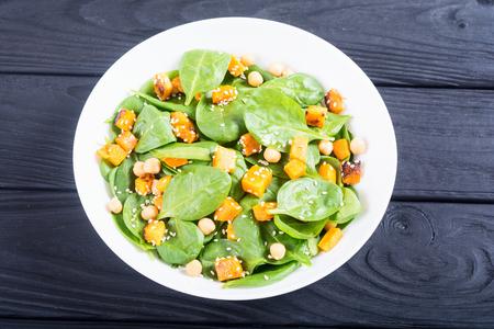 Bord met herfstsalade met pompoen, spinazie, kikkererwten en sesam. Voedsel veganistische achtergrond Stockfoto