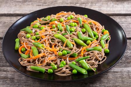 Soba noodles salad . Asian food background . Japanese bowl