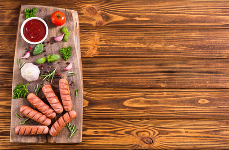 Fried sausages with herbs , spices and ketchup . Food background
