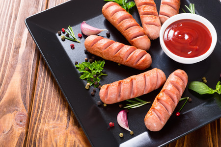 Fried sausages with herbs , spices and ketchup . Food background Banco de Imagens