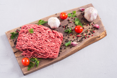 Raw minced beef meat with spices and herbs . Food background