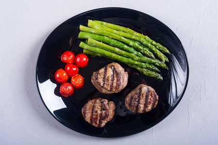 Grilled filet Mignon with asparagus and tomatoes . Beef steak on rustic background