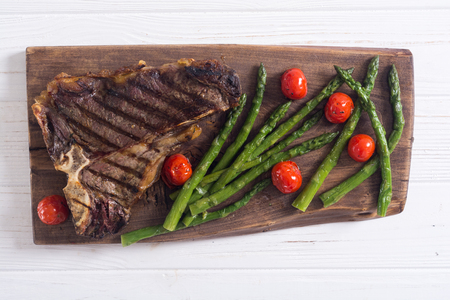 Grilled T-bone steak with asparagus and cherry tomatoes . T bone beef