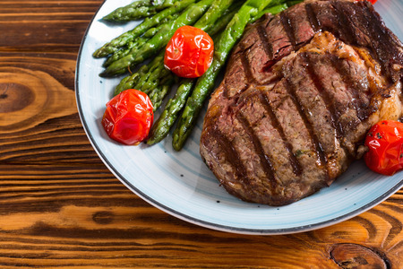 Grilled beef steak rib eye with cherry tomatoes and asparagus . Food background