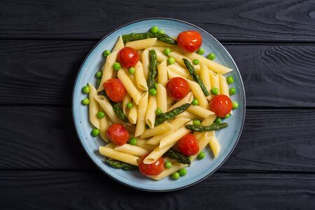 Ensalada de pasta penne con espárragos, tomates y guisantes. Fondo de comida Foto de archivo