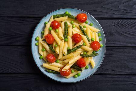 Penne-Nudelsalat mit Spargel, Tomaten und Erbsen. Lebensmittelhintergrund Standard-Bild