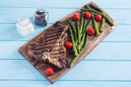 Grilled T-bone steak with asparagus and cherry tomatoes .