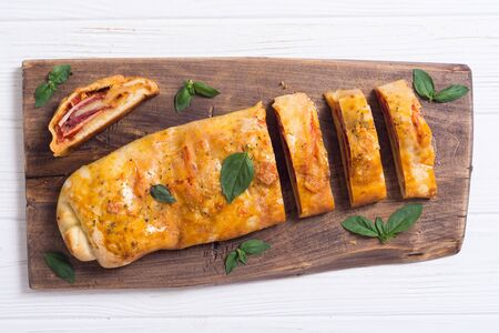 Italian food Pizza roll stromboli with cheese , salami , olives and tomatoes