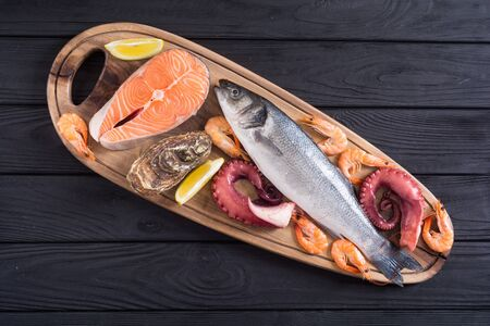 Seafood background . Salmon , sea ​​bass , oysters and octopus