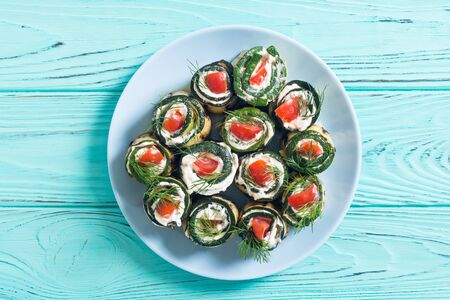 Zucchini rolls with cream cheese , tomatoes and dill . Healthy vegetarian food background