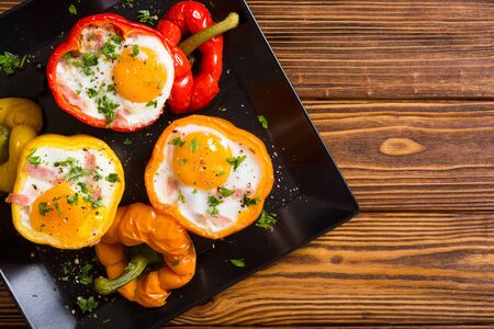 Baked pepper stuffed with bacon and eggs . Food background