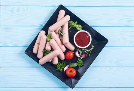 Raw beef sausages with pepper , herbs and ketchup . Food background