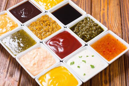 Set of different sauces in ceramic bowl on rustic background